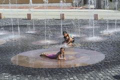 Children on a sunny warm day playing outside in a water fountain. Children happily in shallow clean water on of city fountain on royalty free stock photography