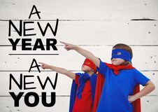 Children in super hero costumes pointing at new year greeting quotes Royalty Free Stock Photos