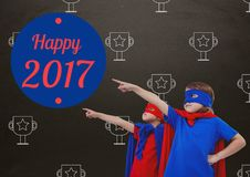 Children in super hero costumes pointing at new year greeting quotes Stock Image