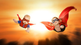 Children superheroes flying across sunset sky royalty free stock photo