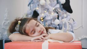 Close-up 4k vidoe of sweet girl sleeping on big Christmas present, looking amazing.