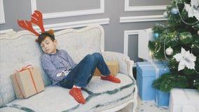 Lovely timelapse of little boy with reindeer headgear, sleeping on the sofa near Christmas presenst and fir-tree.