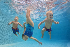 Children swim and dive underwater with fun in swimming pool