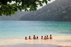 Children swim happily together in the sea of Surin Island. Royalty Free Stock Image