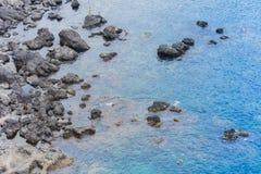 Children swim near rocky sea shore of Acitrezza, Catania, Sicily, Italy royalty free stock photos