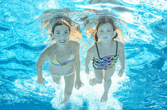 Children swim in pool underwater, girls have fun in water Royalty Free Stock Photography