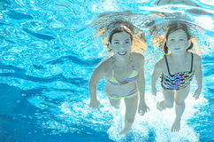 Children swim in pool underwater, girls have fun in water. Children swim in pool underwater, happy active girls have fun in water, kids sport on family vacation royalty free stock photography