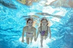 Children swim in pool underwater, girls have fun in water Stock Photos