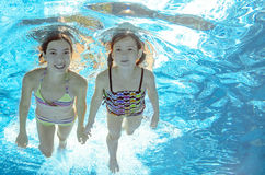 Children swim in pool underwater, girls have fun in water Stock Images