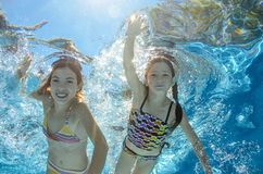 Children swim in pool underwater, girls have fun in water. Children swim in pool underwater, happy active girls have fun in water, kids sport on family vacation Royalty Free Stock Image