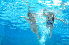Children swim in pool underwater, girls have fun in water Royalty Free Stock Images