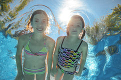 Children swim in pool underwater, girls have fun in water. Children swim in pool underwater, happy active girls have fun in water, kids sport on family vacation royalty free stock photos