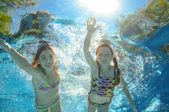 Children swim in pool underwater, girls have fun in water. Children swim in pool underwater, happy active girls have fun in water, kids sport on family vacation Stock Image