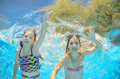 Children swim in pool underwater, girls have fun in water Stock Photography