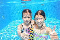 Children swim in pool underwater, girls have fun in water, Stock Image