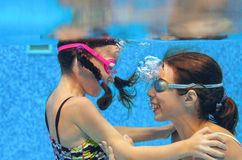 Children swim in pool underwater, happy active girls in goggles have fun under water, kids sport Royalty Free Stock Image
