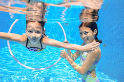 Children swim in pool underwater, happy active girls have fun under water. Kids sport on family vacation stock images