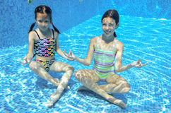 Children swim in pool underwater, happy active girls have fun under water. Kids sport on family vacation Royalty Free Stock Photo