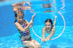 Children swim in pool underwater, happy active girls have fun under water, kids sport Stock Image