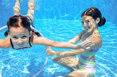 Children swim in pool underwater, happy active girls have fun under water, kids sport Stock Images