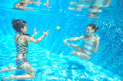 Children swim in pool underwater, happy active girls have fun under water, kids sport Royalty Free Stock Images