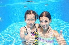 Children swim in pool underwater, happy active girls have fun under water, kids sport Royalty Free Stock Image