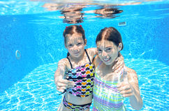 Children swim in pool underwater, happy active girls have fun under water Royalty Free Stock Images