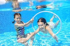 Children swim in pool underwater, happy active girls have fun under water Stock Photo