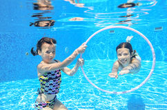 Children swim in pool underwater, happy active girls have fun under water. Kids sport on family vacation stock photography