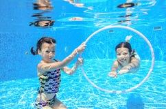 Children swim in pool underwater, happy active girls have fun under water Stock Photography