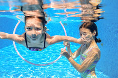 Children swim in pool underwater, happy active girls have fun under water. Kids sport on family vacation stock photos