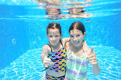 Children swim in pool underwater, happy active girls have fun under water. Kids sport on family vacation royalty free stock photography