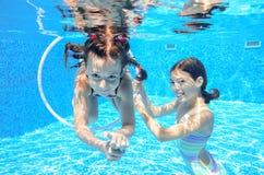Children swim in pool underwater, happy active girls have fun under water. Kids sport on family vacation stock image
