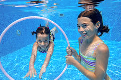 Children swim in pool underwater, happy active girls have fun under water Royalty Free Stock Images