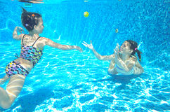 Children swim in pool underwater, happy active girls have fun under water. Kids sport on family vacation stock photo