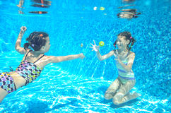 Children swim in pool underwater, happy active girls have fun under water. Kids sport on family vacation royalty free stock image