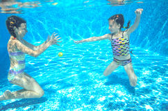 Children swim in pool underwater, happy active girls have fun under water Stock Photography