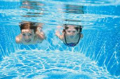 Children swim in pool underwater, happy active girls have fun in water, kids fitness and sport on family vacation Stock Images