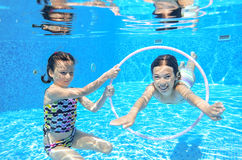 Children swim in pool underwater. Happy active girls have fun in water, kids sport on family vacation royalty free stock image