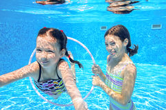 Children swim in pool underwater. Happy active girls have fun in water, kids sport on family vacation stock image