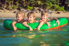 Children swim in the sea on an inflatable mattress and have fun.  royalty free stock photo