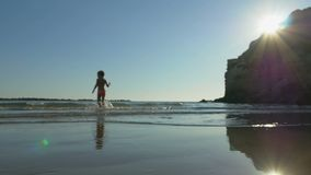 Children swim in the sea at sunset. A little girl runs into the sea to swim in evening warm water. Evening beach, sea waves and sunset. Low-angle shot in slow stock footage