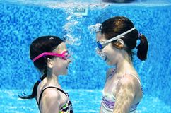 Children swim in swimming pool underwater, happy active girls have fun under water, kids fitness and sport royalty free stock photo