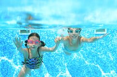Children swim in swimming pool underwater, happy active girls have fun under water, kids fitness and sport. On active family vacation Royalty Free Stock Photo