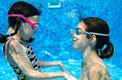 Children swim in swimming pool underwater, happy active girls have fun under water, kids fitness and sport royalty free stock images