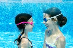 Children swim in swimming pool underwater, happy active girls have fun under water, kids fitness and sport stock image