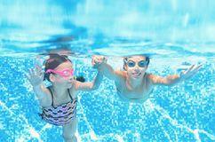 Children swim in swimming pool underwater, happy active girls have fun under water, kids fitness and sport on family vacation. Children swim in swimming pool royalty free stock photo