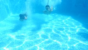 Children swim under water. 4k. Slow motion. boy and girl diving into the water together stock video footage