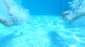 Children swim under water. 4k. Slow motion. boy and girl diving into the water together stock footage