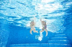Children swim underwater in swimming pool, happy active girls have fun under water, kids fitness and sport. On active family vacation royalty free stock photography